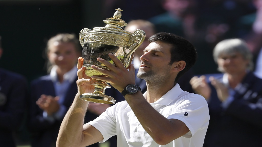 In this July 15, 2018 file picture, Serbia's Novak Djokovic lifts the trophy after winning the men's singles final against Kevin Anderson, of South Africa, at the Wimbledon Tennis Championships in London.