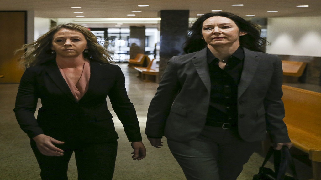 Former Dallas police Officer Amber Guyger, left, walks the hallway at the Frank Crowley Courts Building in Dallas on Thursday, June 6, 2019. (Ryan Michalesko/The Dallas Morning News via AP)