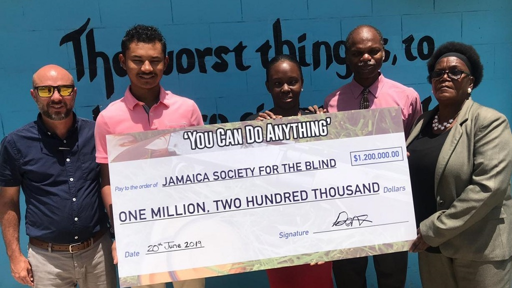 Danzell Knight (left) organiser of the You Can Do Anything charity sporting clays tournament and Bruce DuQuesnay (2nd left) of the Jamaica Skeet Club present a  symbolic cheque for $1.2 million to Mary Mitchell-Coombs (right) of the Jamaica Society for the Blind.