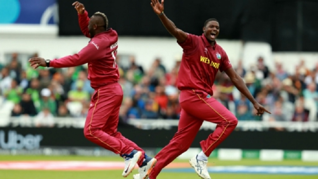 Andre Russell and Jason Holder celebrate the latter's dismissal of Imad Wasim.