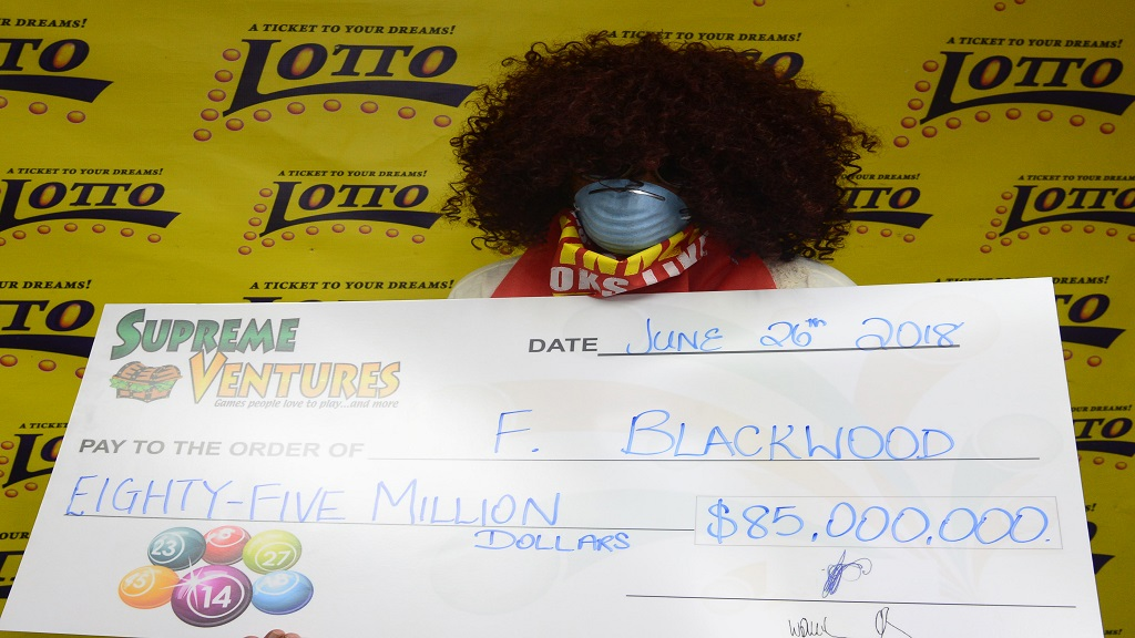: Lotto winner, F. Blackwood holds a symbolic cheque representing the $85 million Lotto jackpot won on Saturday, June 16, 2018 for draw #1481.