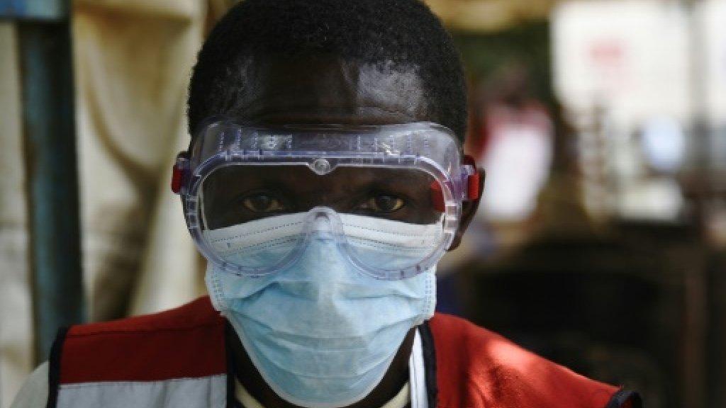 Un membre des équipes luttant contre l'épidémie d'Ebola porte un masque dans un centre sanitaire installé à la frontière de l'Ouganda et de la RDC, le 13 juin 2019. Un membre des équipes luttant contre l'épidémie d'Ebola porte un masque dans un centre sanitaire installé à la frontière de l'Ouganda et de la RDC, le 13 juin 2019. AFP/Archives