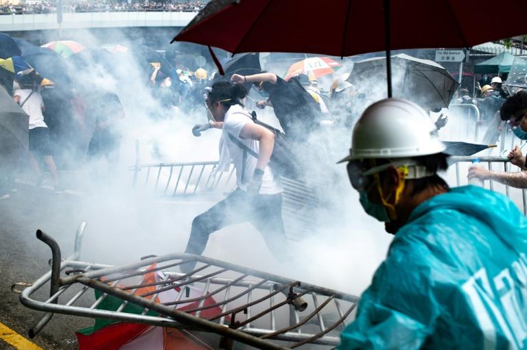 Des protestataires prennent la fuite après des gaz lacrymogènes tirés par la police, le 12 juin 2019 à Hong Kong, lors d'une manifestation contre un projet de loi autorisant les extraditions vers la Chine continentale. AFP / Philip FONG