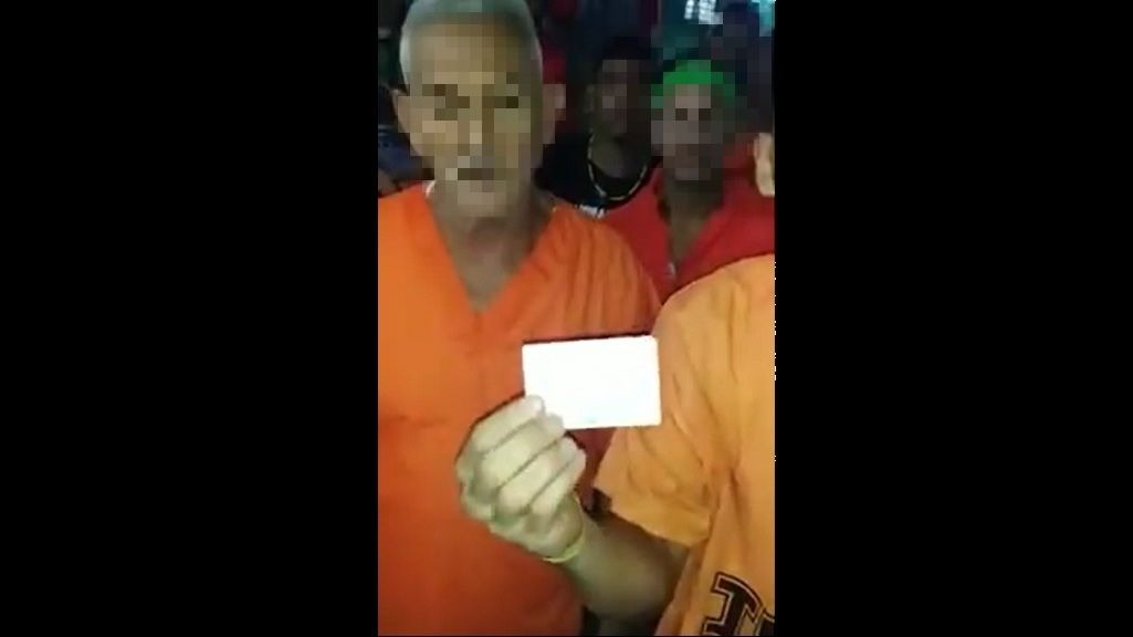 Photo: An elderly detainee at the Immigration Detention Centre showed a card he received from the Living Water Community as proof he is an asylum seeker. A video of the group was shared to social media on June 4, 2019, with inmates vowing to go on a hunger strike until they are freed.