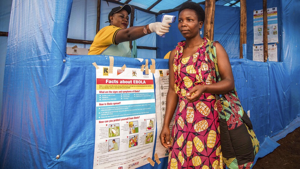 In this photo provided by the International Rescue Committee, a Congolese refugee is screened for Ebola symptoms at the IRC triage facility in the Kyaka II refugee settlement in Kyegegwa District in western Uganda, Thursday, June 13, 2019.  (Kellie Ryan/International Rescue Committee via AP)