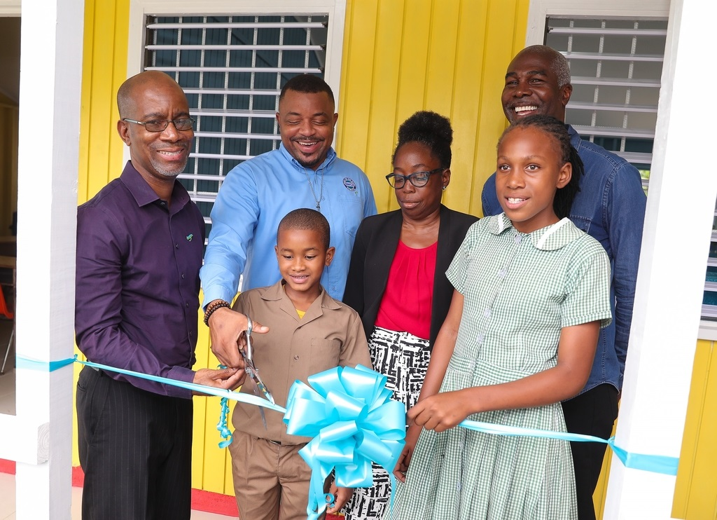 : (From left) Willard Brown, Executive Vice President, Employee Benefits Division, Sagicor Life and Marcus Irons, Project Manager, Food for the Poor, are assisted by students Morsell Weir and Melisha Brown, in cutting a ribbon to officially open a new block of classrooms at the St Christopher's School for the Deaf in Brown's Town, St Ann.
