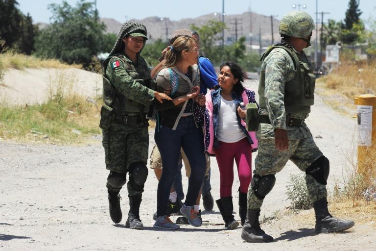 Des membres de la Garde nationale mexicaine arrêtent des femmes et une fillette s'apprêtant à franchir le Rio Bravo entre Ciudad Juarez au Mexique et El Paso aux Etats-Unis, le 21 juin 2019