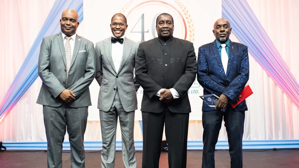 Minister of Transport, Robert Montague (second from the right) poses alongside, (from the left) Aeronautical Telecommunications Limited, AEROTEL's General Manager, Howard Armstrong, Chairman of the board, Marc Ramsay and longest serving staff member, Operations Manager for the Kingston Region, Rowell Hall at the company's 40th anniversary long service awards and banquet.