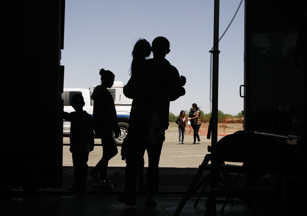 In this Wednesday, May 22, 2019 file photo migrants mainly from Central America guide their children through the entrance of a World War II-era bomber hanger in Deming, N.M. (AP Photo/Cedar Attanasio, File)
