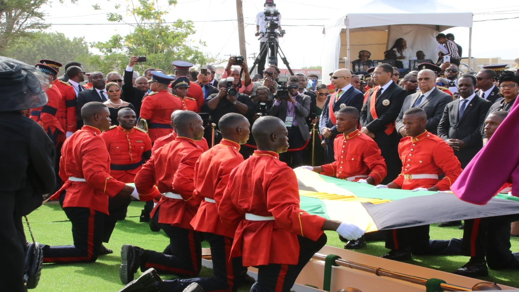 The bearer party of the Jamaica Defence Force conducts the ceremonial folding of the National Flag which draped the casket of former Prime Minister Edward Seaga, during the burial in national Heroes Park on Sunday in Kingston.