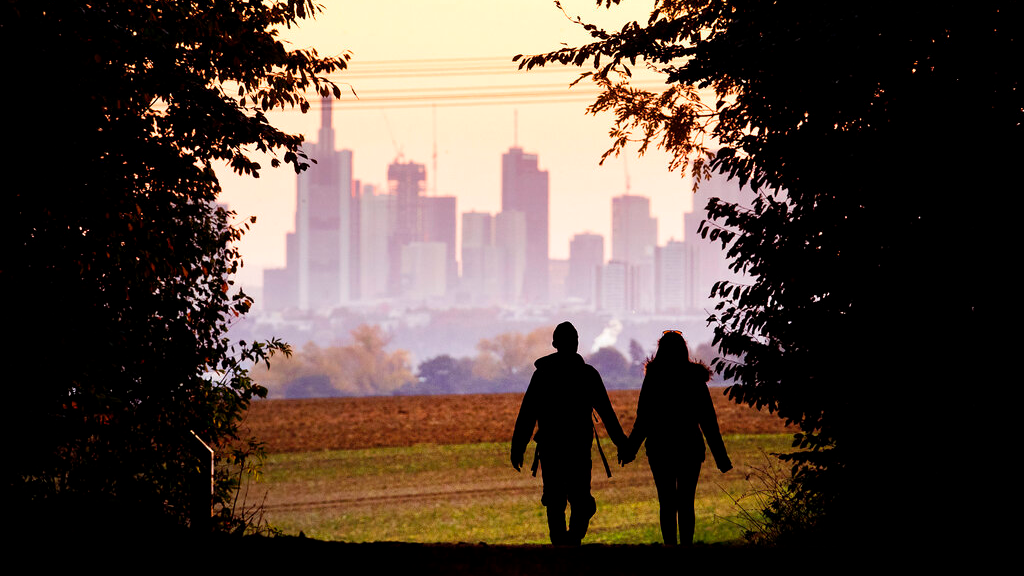 In this Oct. 21, 2018, file photo, a couple walks through a forest with the Frankfurt skyline in background near Frankfurt, Germany. (AP Photo/Michael Probst, File)
