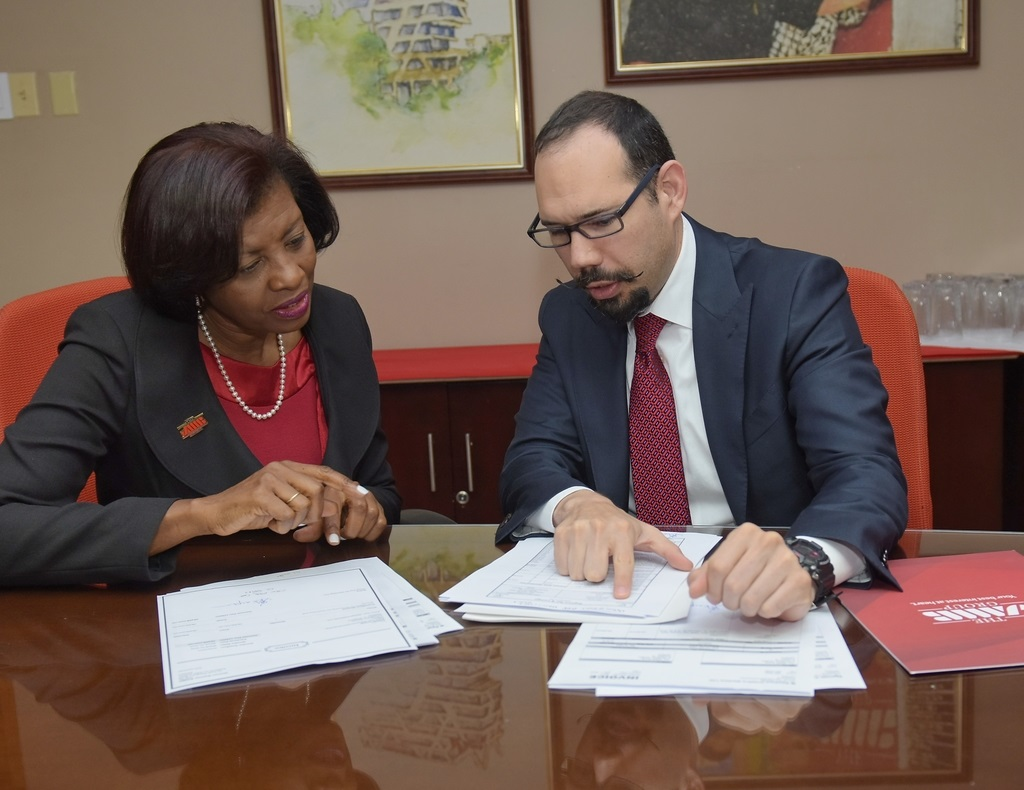 JMMB Money Transfer CEO, Sharon Gibson (left) and Erick Schneider, VP of Business Development for Latin America and the Caribbean, WorldRemit goes through the details of their collaborative performance during a partnership visit by WorldRemit.