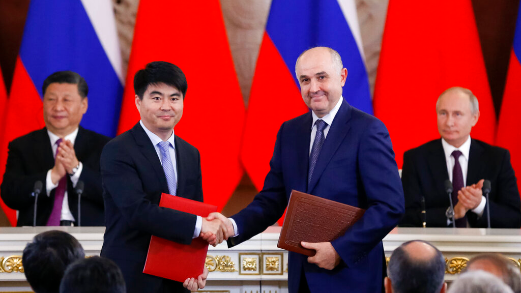 Guo Ping, deputy Chairman of Huawei Technologies Co Ltd, foreground left, shakes hands with Russian President of MTS mobile network operator, Alexei Kornya as Russian President Vladimir Putin, right, and Chinese President Xi Jinping attend a signing ceremony following their talks in the Kremlin in Moscow, Russia, Wednesday, June 5, 2019. (AP Photo/Alexander Zemlianichenko, Pool)