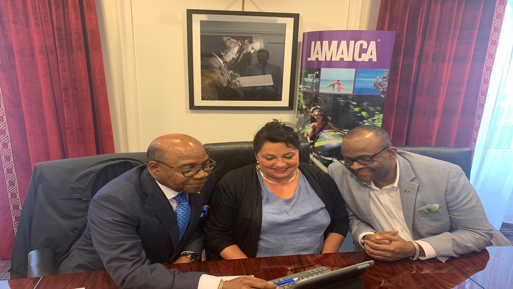 Maureen Lachant, Business Development Manager from Les Maisons du Voyage (centre) sharing the current Jamaica campaign on the Les Maisons du Voyage website to The Hon. Edmund Bartlett, Jamaica's Minister of Tourism (left) and Donovan White, Jamaica's Director of Tourism (right).