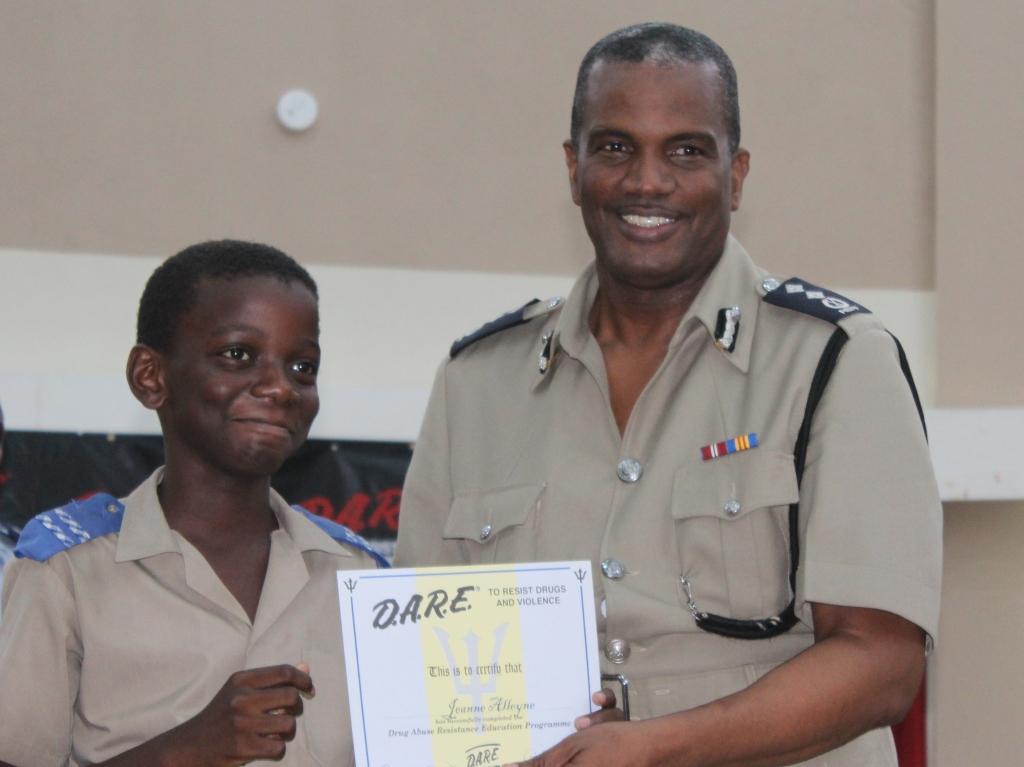 Deputy Commissioner, Erwin Boyce presenting Jeanne Alleyne with his DARE Programme certificate.