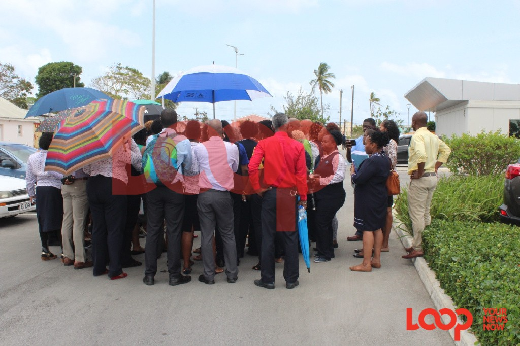 Striking CXC workers huddle for talks with representatives of the Barbados Workers' Union earlier this afternoon