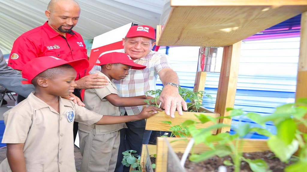 Two students from White Marl Primary School in St Catherine - Cheandre Codner and Usain Duffus -  assisting Col Jaimie Ogilvie, Assistant Vice President, Hi-Pro Division, Jamaica Broilers Group (left, background) and Agriculture Minister, Audley Shaw, in demonstrating at the recent Denbigh show launch, how easy it is to grow food crops in small spaces using recycled materials such as an empty paint can.