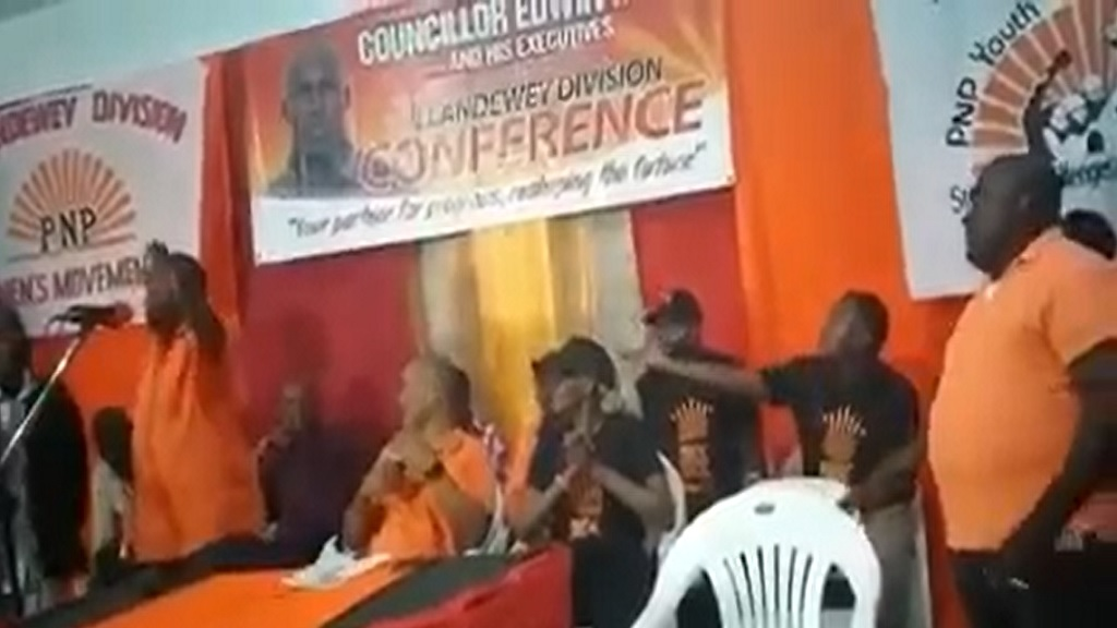 Hubert Williams (left), Councillor for the White Horses Division addresses Comrades from the podium at a PNP meeting on Sunday. Seated beside him is PNP prospective presidential candidate Peter Bunting.