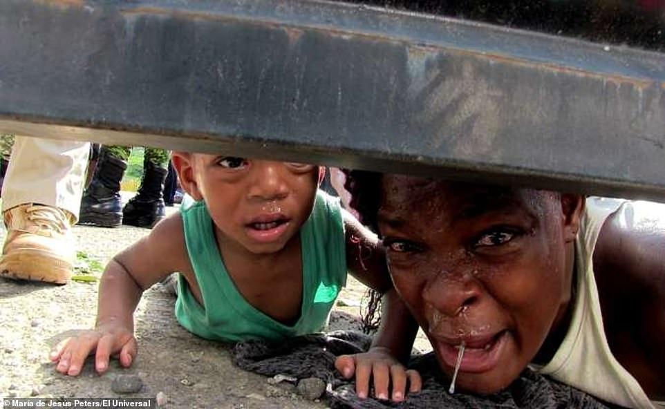 La mère haïtienne demandant de la nourriture, de l'eau potable et des soins médicaux pour son fils de cinq ans malade alors que celui d'un an rampait au sol à coté d'elle./Photo: Maria de Jesus Peters-El Universal.
