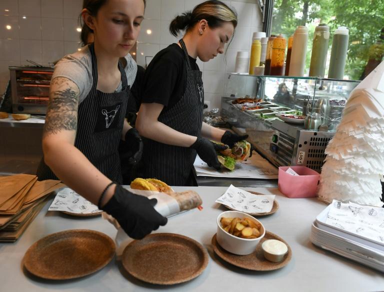 Des femmes servent à manger sur des assiettes comestibles dans un restaurant vegan de Varsovie, le 29 mai 2019