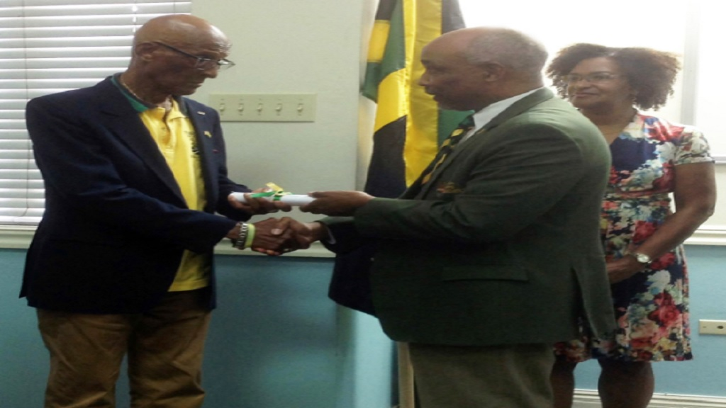 President of the Jamaica Olympic Association (JOA), Christopher Samuda (right) presents an Olympic Pin to Olympian Byron LaBeach at a ceremony on Sunday, June 16 at the offices of the JOA.