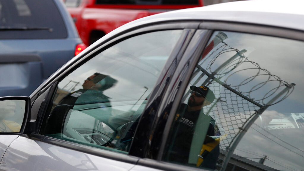 Customs and Border Protection agents are reflected in the window of an entering car, as they survey vehicles entering the U.S. on the Puerta Mexico international bridge leading into Brownsville, Texas from Matamoros, Mexico, Friday, June 28, 2019. (AP Photo/Rebecca Blackwell)
