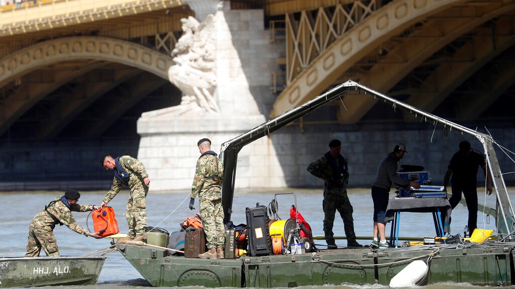 Rescue team members are seen on a barge floating on the Danube river where a sightseeing boat capsized in Budapest, Hungary, Saturday, June 1, 2019. (AP Photo/Laszlo Balogh)