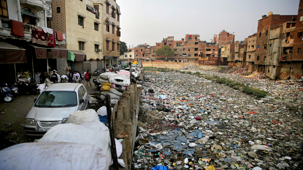 In this Saturday, Dec. 8, 2018 photo piles of electronic waste is placed next to a drain chocked with plastic and garbage in New Delhi, India. (AP Photo/Altaf Qadri)