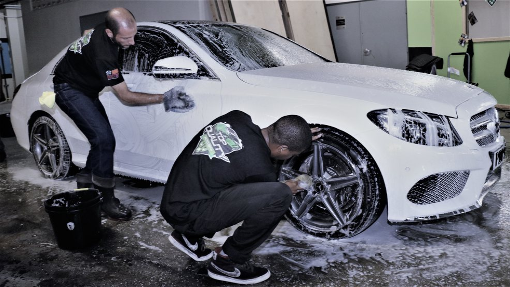 Employees of Top Quality Auto Spa cleaning a car.