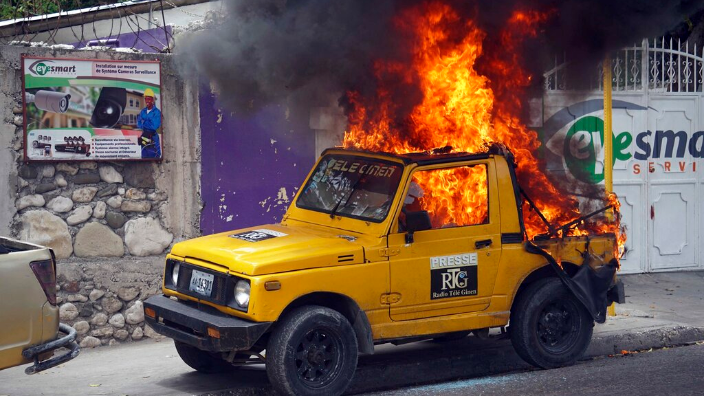 A car that belongs to Radio Tele-Ginen burns during a protest demanding the resignation of President Jovenel Moise in Port-au-Prince, Haiti, Monday, June 10, 2019. Opposition leaders in Haiti launched a two-day strike that paralyzed the country's capital amid another day of protests demanding that President Jovenel Moise resign over corruption allegations. (AP Photo/Edris Fortune)
