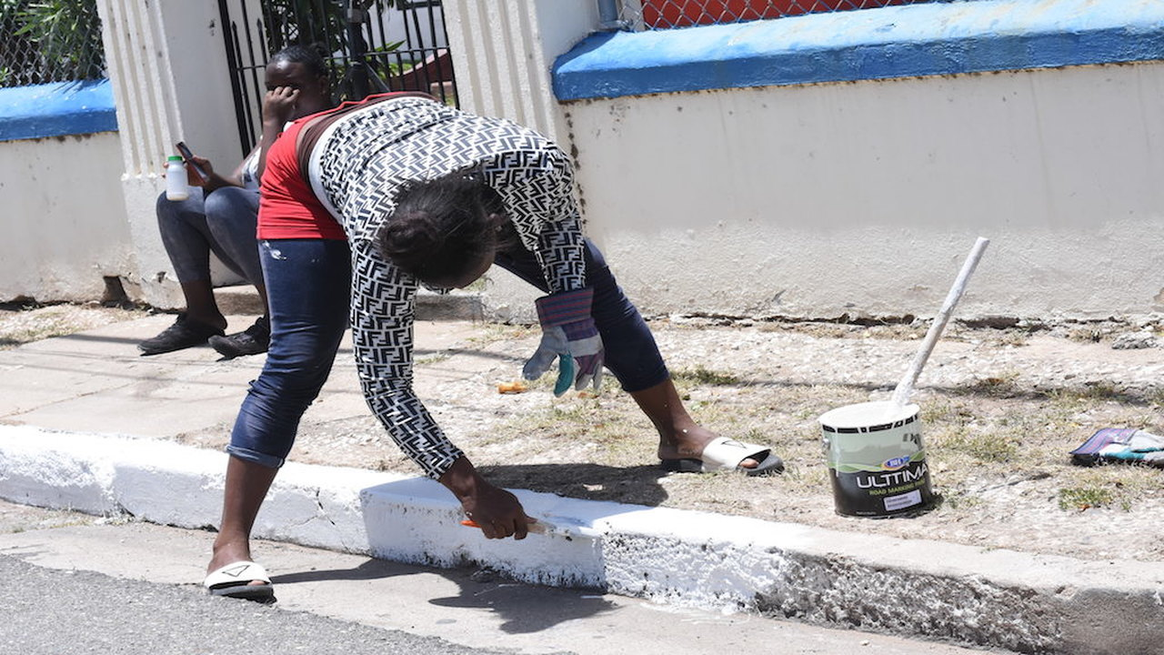 A member of a work crew busy painting a sidewalk along a roadway in the general area where funeral activities are scheduled to take place for former Prime Minister, Edward Seaga, in downtown Kingston on Sunday.  (Photos: Marlon Reid)