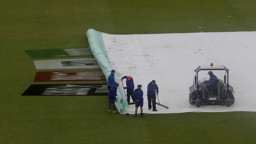 Ground staff work to clear the rain covers on the pitch after play was stopped due to rain during the World Cup cricket match between South Africa and the West Indies at The Ageas Bowl in Southampton, Monday, June 10, 2019. (AP Photo/Kirsty Wigglesworth)