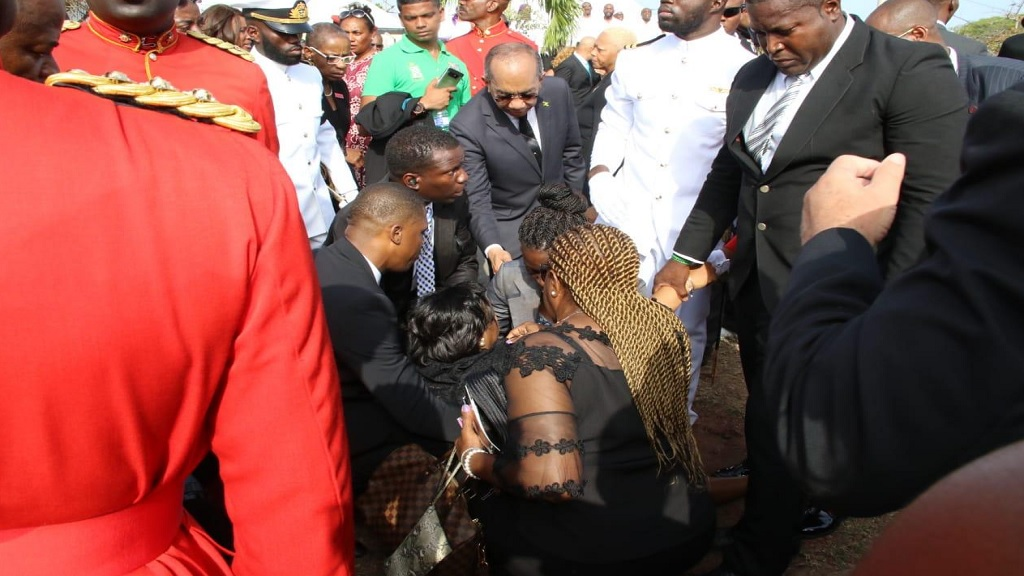 Concerned persons gather around the Premier of the Turks and Caicos Islands after she collapsed at the graveside on Sunday, shortly after the interment of Edward Seaga at the National Heroes Park.
