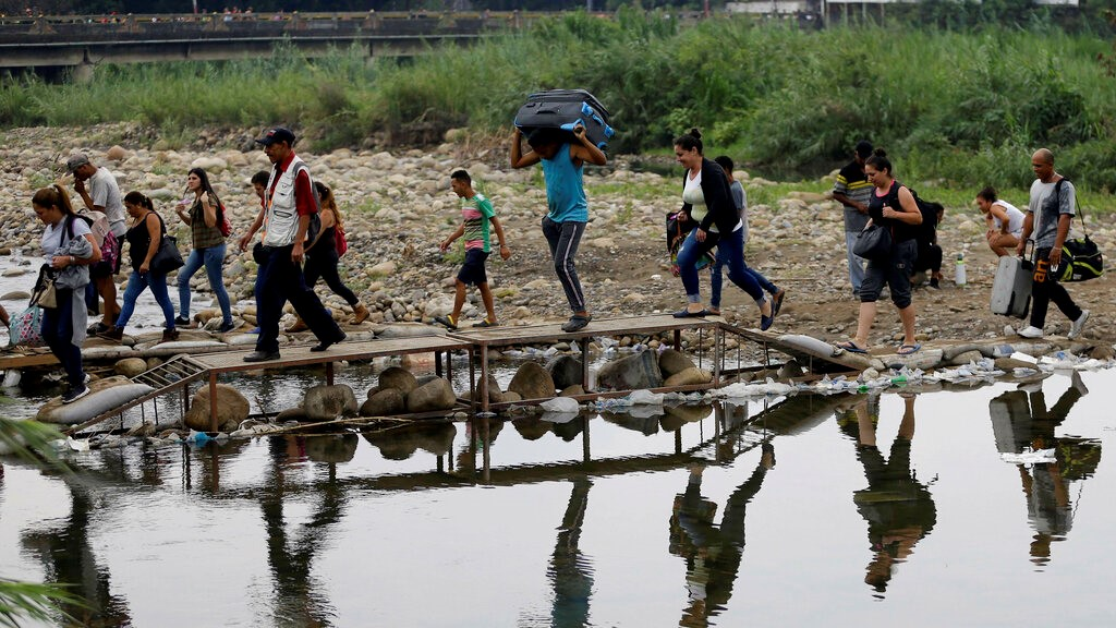 In this April 14, 2019 file photo, Venezuelans cross illegally into Colombia near the Simon Bolivar International Bridge, close to Cucuta, Colombia. (AP Photo/Fernando Vergara, File)