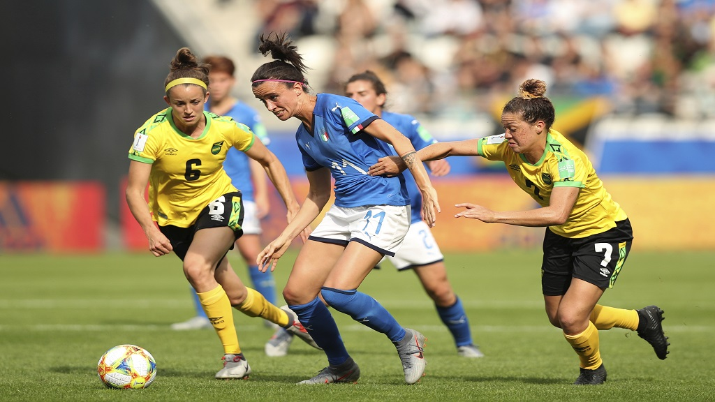 Italy's Barbara Bonansea, center, goes for the ball between the Jamaica pair of Havana Solaunj, left, and Chinyelu Asher during the Women's World Cup Group C football match  at the Stade Auguste-Delaune in Reims, France, Friday, June 14, 2019.