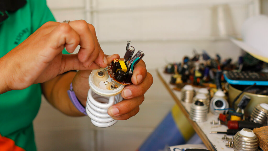 Eliset González repairs a broken lightbulb for a customer who cannot afford a new one at her marketplace kiosk in Caracas, Venezuela, Sunday, May 5, 2019. (AP Photo/Ariana Cubillos)
