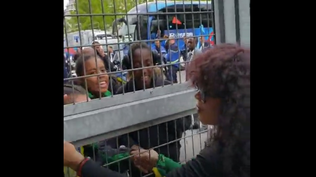 Reggae Girlz Ambassador, Cedella Marley, greeting the team members after their game against Brazil on Sunday through a fence at the stadium as a result of accreditation issues which she encountered.
