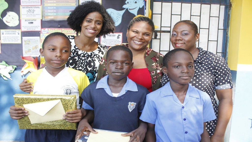 (Front row l-r) Jaheem Clarke, Akeem Hunter and Kahlil Edwards display their gifts that they receive from candidate in Central Kingston Imani Duncan Price (back row left) for completing the World Robotics Olympiad. Also present is Robotics Coach Sakoya Graf Watson (centre) and School Principal La-Toya Nesbitt.