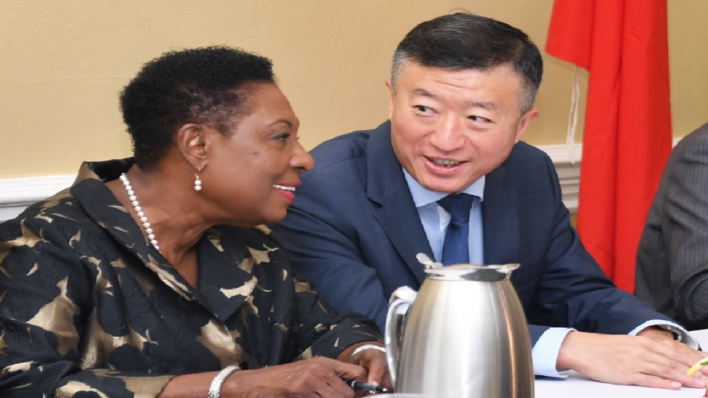 Sports Minister Olivia Grange (left) shares a light moment with the Ambassador of the People's Republic of China to Jamaica, His Excellency Tian Qi.  They were at the official send-off for the second batch of 138 Jamaican athletes and coaches who will receive specialised training in China under a sports cooperation agreement between both countries.
