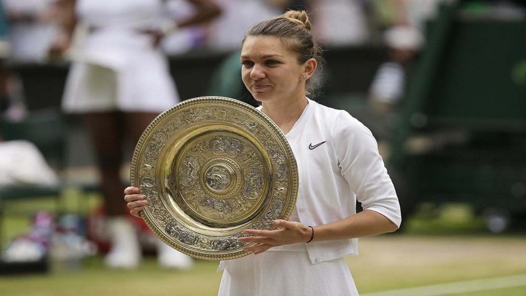 Romania's Simona Halep holds her trophy after defeating United States' Serena Williams in the women's singles final match on day twelve of the Wimbledon Tennis Championships in London, Saturday, July 13, 2019. (AP Photo/Tim Ireland).