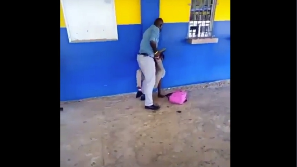 A screen grab from a video of a 'teacher' and a student engaged in a tussle about a pair of pink socks that the student wore to school.