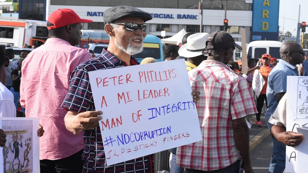 PNP Senator KD Knight displays a placard that likens 'sticky fingers' to the JLP during his party's protest on Thursday. (PHOTOS: Marlon Reid)