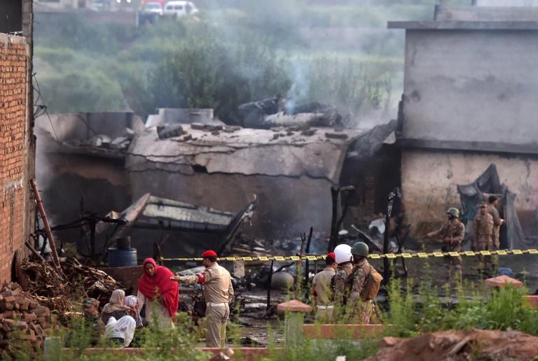 QURESHIDes habitants dans les décombres de leur maison alors que des soldats établissent un périmètre de sécurité autour de la zone habitée où s'est écrasé un petit avion militaire, à Rawalpindi (Pakistan) le 30 juillet 2019