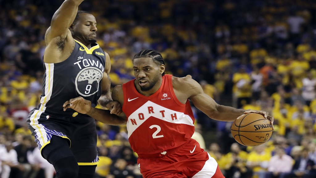 In this June 13, 2019, file photo, Toronto Raptors forward Kawhi Leonard (2) drives against Golden State Warriors forward Andre Iguodala (9) during the first half of Game 6 of basketball's NBA Finals in Oakland, Calif.