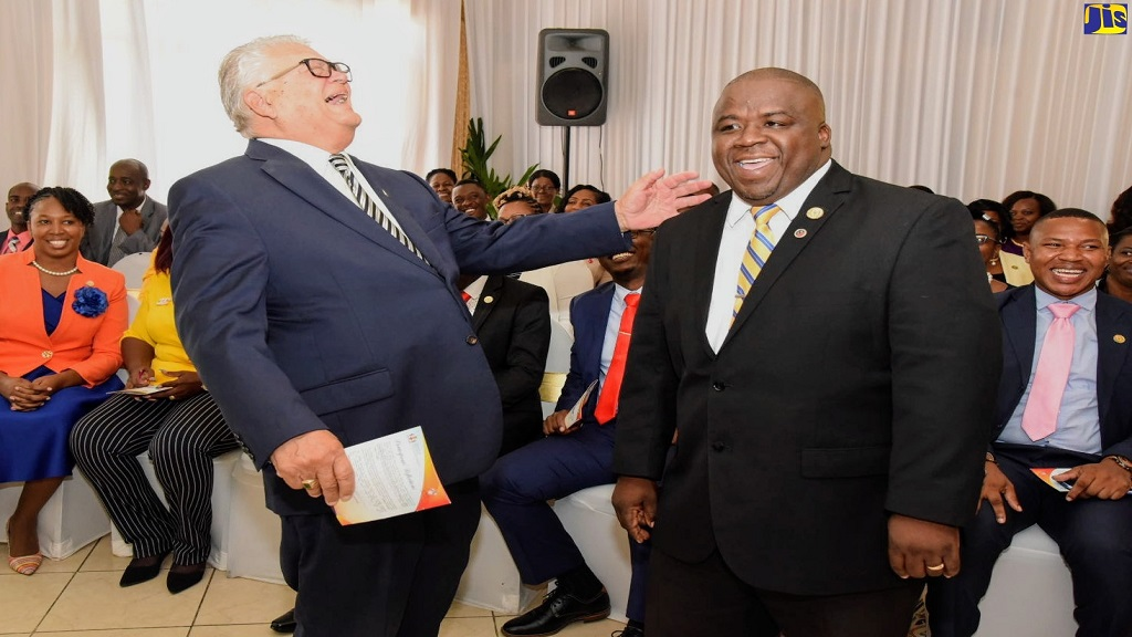 Minister with responsibility for Education, Karl Samuda (left), shares a light moment with Everton Tyndale, a participant in the Aspiring Principals' Programme (APP), at the programme's presentation ceremony on Tuesday at the Mona Visitors' Lodge, University of the West Indies (UWI), Mona Campus