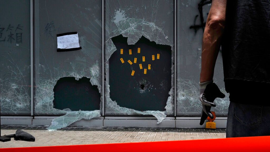 Photo: A police officer stands guard near the broken glasses outside Legislative Council building in Hong Kong, Tuesday, July 2, 2019. Hundreds of protesters swarmed into Hong Kong's legislature Monday night, defacing portraits of lawmakers and spray-painting pro-democracy slogans in the chamber before vacating it as riot police cleared surrounding streets with tear gas and then moved inside. (AP Photo/Vincent Yu)