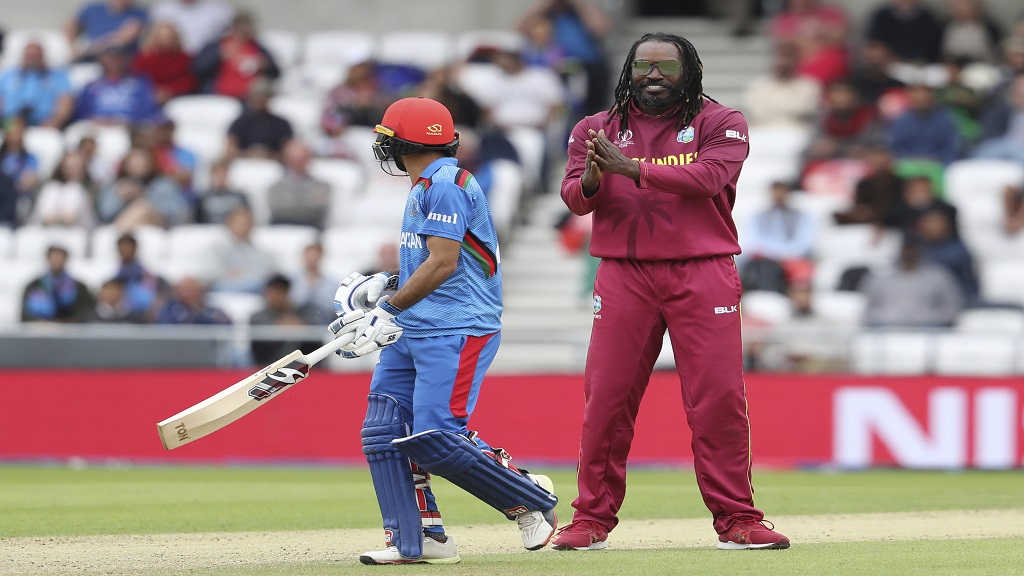 West Indies' Chris Gayle, right, celebrates the dismissal of Afghanistan's Ikram Ali, left, during the Cricket World Cup match  at Headingley in Leeds, England, Thursday, July 4, 2019. (AP Photo/Rui Vieira)