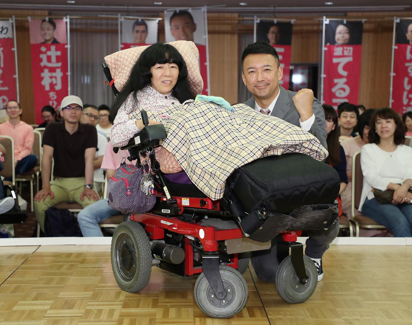 """Taro Yamamoto, leader du nouveau parti d'opposition """"Reiwa Shinsengumi"""" et la candidate du parti Eiko Kimura, atteinte d'une paralysie d'origine cérébrale, après l'élection de cette dernière au Sénat japonais, le 22 juillet 2019 à Tokyo afp.com - JIJI PRESS"""