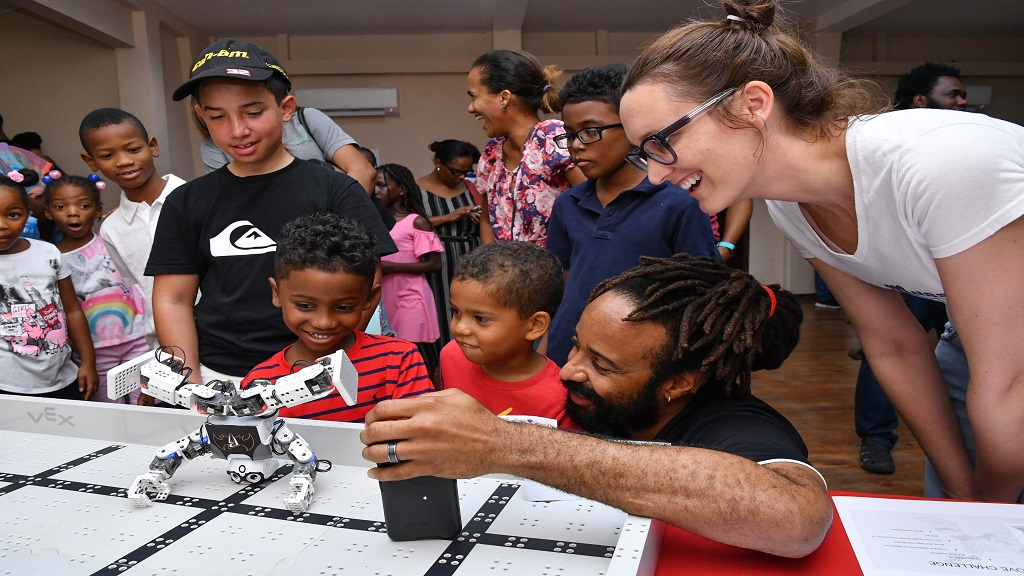 Chairman of Musson Foundation, Melanie Subratie looks on as Halls of Foundation founder, Marvin Hall demonstrates the Robotic Mini to an excited group of students.