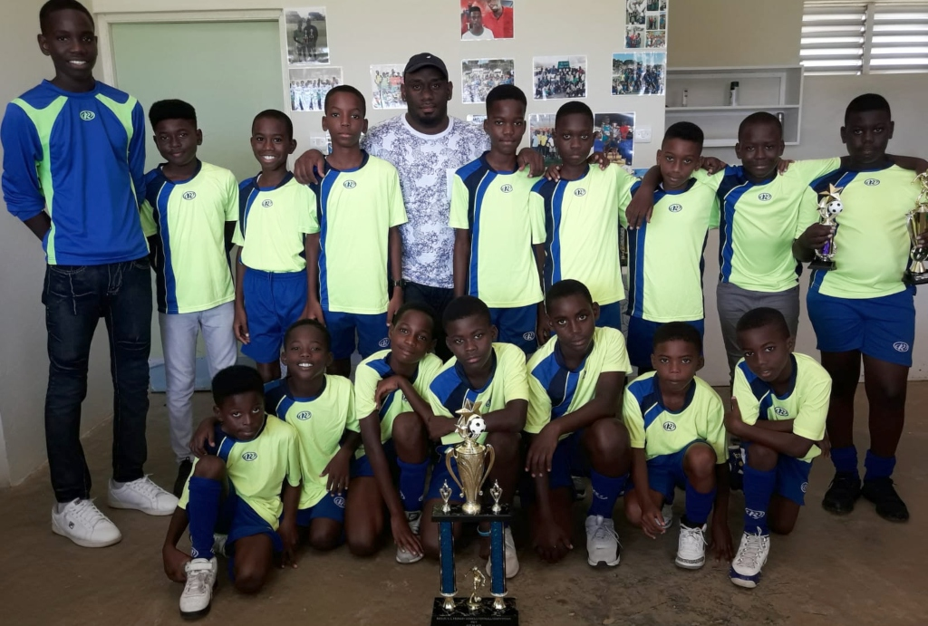 All Saints Primary footballers and coach just collecting gold trophies.